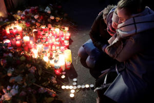 Two women mourn beside candles in Berlin, Germany, Tuesday, Dec. 20, 2016, the day after a truck ran into a crowded Christmas market nearby and killed several people.