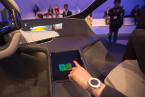 An exhibitor touches over a HoloArchive hologram in the Inside Future concept sculpture of an interior for BMW during CES in Las Vegas.