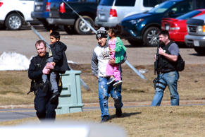 Police officers escort a family from the apartment complex to safety Wednesday, March 22, 2017, in Rothschild, Wis. The shootings happened at a bank, a law firm and an apartment complex, where officers, including a SWAT team, were in a standoff with the suspect late in the afternoon, Wausau police Capt. Todd Baeten said at a news conference. The area is about 90 miles west of Green Bay.