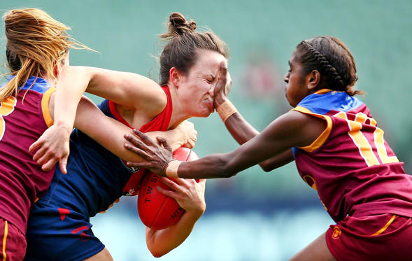 Slide 20 of 34: MELBOURNE, VICTORIA - MAY 22:  Daisy Pearce of Melbourne is tackled by Emily Bates of Brisbane and Delma Gisu of Brisbane during the 2016 AFL Womens match between the Melbourne Demons and the Brisbane Lions at the Melbourne Cricket Ground on May 22, 2016