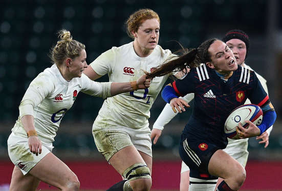 Slide 6 of 34: TOPSHOT - France's scrum half Jade Le Pesq (R) has her hair pulled by England's scrum-half Natasha Hunt (L) during the Six Nations international women's rugby union match between England Women and France Women at Twickenham stadium in south west London o