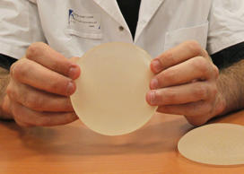 Dr. Maurice Mimoun, a plastic surgeon at the St Louis hospital in Paris holds a silicone gel breast implant made by French company Poly Implant Prothese, or PIP, that he removed from a patient because of concerns that they are unsafe. An independent expert group released a report Wednesday April 24, 2013, which slammed Britain's cosmetic surgery industry for not protecting patients adequately and is calling for stricter controls in the aftermath of a breast implant scandal in Europe last year that left tens of thousands of women with cheap silicone implants prone to ruptures. The expert group, commissioned by the U.K. Department of Health, also called for the creation of a registry of implants and other medical devices. (AP Photo/Michel Euler, File)