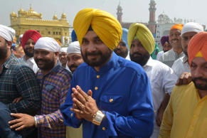 Indian cricketer-turned-politician and Punjab Cabinet Minister Navjot Singh Sidhu (C) gestures as he pays his respects at The Golden Temple in Amritsar on March 22, 2017, after his recent election to office in the northern Indian state of Punjab.