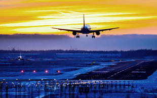 Commercial airliner lands to airport runway at sunset, runway landing lights lit...