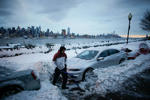 Residents clear their cars and street of snow in Weehawken, New Jersey, as the skyline of Manhattan and the Hudson River are seen after a snowstorm in New York, U.S. March 14, 2017.