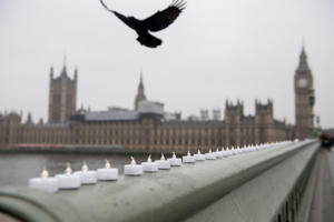 A bird flies over electronic candles left in tribute on Westminster Bridge opposite the Houses of Parliament in central London on March 24, 2017 two days after the March 22 terror attack on the British parliament and Westminster Bridge.