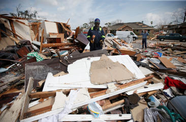 Willie Anderson tries to salvage possessions from his daughter's destroyed home, in the aftermath of Tuesday's tornado that tore through the New Orleans East section of New Orleans, Wednesday, Feb. 8, 2017.