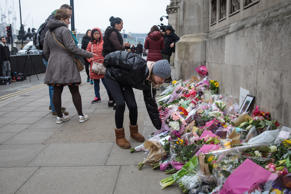 A young woman lays flowers outside the Houses of Parliament following Wednesday'...