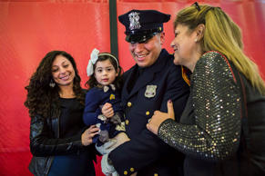 Matias Ferreira, center, celebrates with his 2-year-old daughter, wife, left, and mother during his graduation from the Suffolk County Police Department Academy at the Health, Sports and Education Center in Suffolk, Long Island, N.Y., Friday, March 24, 2017.