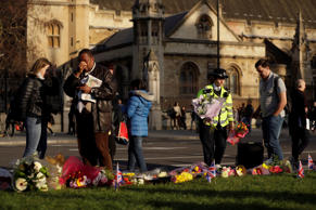 A police officer places flowers as a man gestures beside floral tributes to vict...