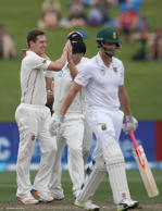 Matt Henry of New Zealand, (L) celebrates the wicket of Theunis de Bruyn of South Africa.