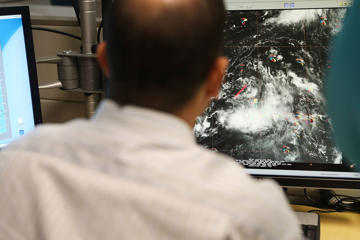 FILE: A hurricane specialist at the National Hurricane Center tracks the path of a weather disturbancein the northern Caribbean islands and surrounding waters on August 25, 2016 in Miami, Florida.