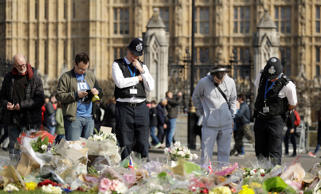 Police officers and members of the public look at the floral tributes to the victims of the Westminster attack placed outside the Palace of Westminster, London, Monday March 27, 2017.