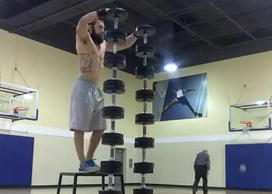 Man does handstand on dumbbell tower
