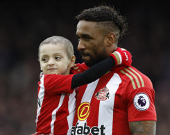 Jermain Defoe carries out young Sunderland fan Bradley Lowery before the match.