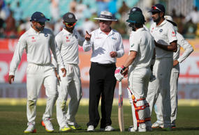 Umpire Ian Gould (C) of England talks to India's Karun Nair (L) after an argument.