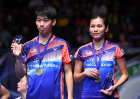 Malaysia's Peng Soon Chan (L) and Malaysia's Liu Ying Goh (R) pose on the podium with their runners-up trophies after their defeat to China's Lu Kai and China's Huang Yaqiong after their All England Open Badminton Championships mixed doubles final match in Birmingham, central England.