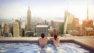 Couple relaxing in swimming pool on hotel rooftop.