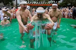 Men wearing loin cloths hold on to ice as they bathe in ice-cold water outside the Teppozu Inari shrine in Tokyo, Japan, January 8, 2017. According to organizers, about 100 participants took part in the Shinto ceremony to purify their souls and wish for