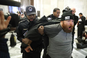 WASHINGTON, DC - JANUARY 10:  A protester shouts, 'No Trump, No KKK, No facist USA' as he is hauled out of the Senate Judiciary Committee's confirmation hearing for Sen. Jeff Sessions (R-AL) to be the next U.S. Attorney General in the Russell Senate Offi