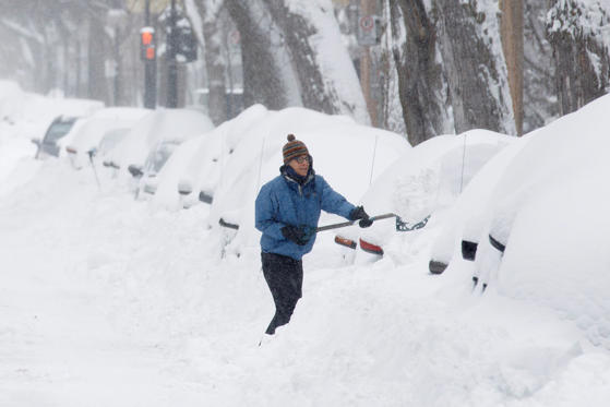 Slide 1 of 8: A woman clears snow away from her car in Montreal that was buried in snow as a late winter storm.