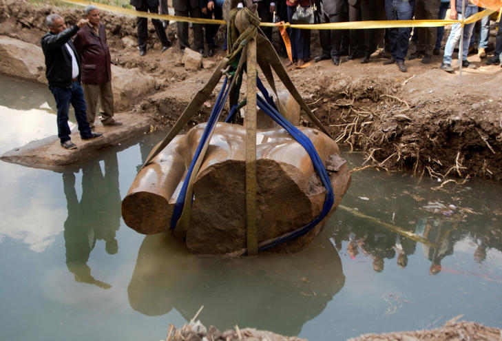 A massive statue is pulled out of groundwater in a Cairo slum.