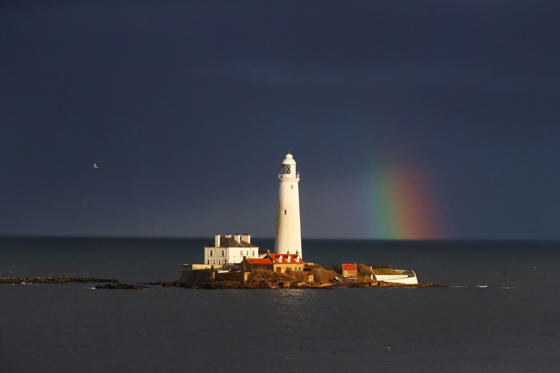 Slide 1 of 20: A rainbow appears next to St. Mary's Lighthouse, Whitley Bay. Spring weather Mar 16th 2017.