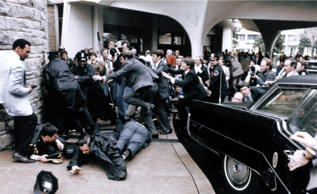 In this March 30, 1981 file photo released by the White House, White House press secretary James Brady, face down at right, and Washington, D.C., police officer Thomas Delahanty, front, lie on the ground after being wounded during the assassination attempt on President Reagan as he was leaving the Washington Hilton, March 30, 1981. (AP Photo/White House, Michael Evans)