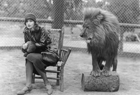 1925:  Swedish-born actress Greta Garbo (1905 - 1990) sits in a chair next to Leo, the lion mascot for MGM studios.  (Photo by Marc Wanamaker/Hulton Archive/Getty Images)