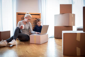 Woman and son sitting inside their new home and having fun during box unpacking. Woman is holding cup of coffee and they are looking at laptop computer in front of them.