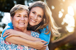 Portrait of a happy mature woman hugging her mother outdoors