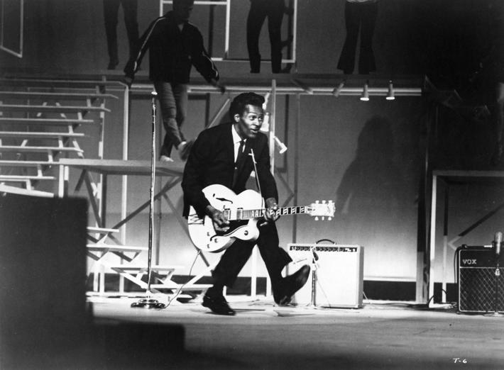 "Slide 7 of 14: SANTA MONICA, CA - DECEMBER 29: Rock and roll guitarist Chuck Berry performs his ""duck walk"" as he plays his electric hollowbody guitar at the TAMI Show on December 29, 1964 at the Santa Monica Civic Auditorium in Santa Monica, California. Other performers included James Browm, The Rolling Stones, The Beatles and Jan & Dean. (Photo by Michael Ochs Archives/Getty Images)"