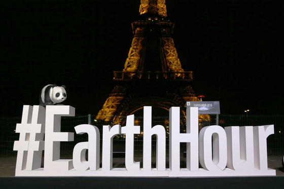Slide 1 of 21: A person dressed as a WWF panda stands near the Eiffel Tower in Paris after it went dark for the Earth Hour environmental campaign on March 19, 2016. / AFP / THOMAS OLIVA        (Photo credit should read THOMAS OLIVA/AFP/Getty Images)