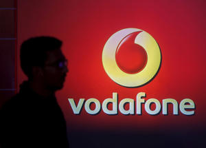 A man casts silhouette onto an electronic screen displaying logo of Vodafone India after a news conference to announce the half year results in Mumbai, India, November 10, 2015.