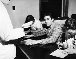 American actor and singer Elvis Presley filling in forms in the exam centre for his induction into the US army, Memphis, Tennessee on March 25, 1958.