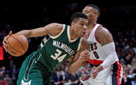 Milwaukee Bucks forward Giannis Antetokounmpo, left, dribbles past Portland Trail Blazers guard Damian Lillard during the first half of an NBA basketball game in Portland, Ore., Tuesday, March 21, 2017.