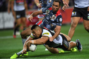 Moses Leota of the Panthers (bottom) tackled by Cameron Smith of the Storm during the match.