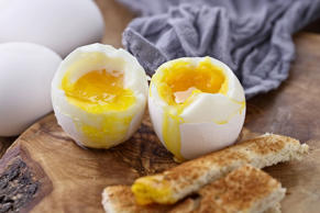 Two soft boiled eggs with toast soldiers against a rustic background. Extreme sh...