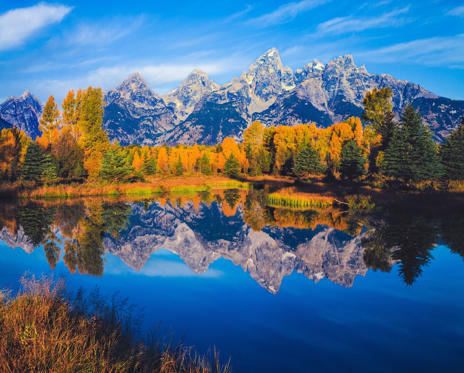 Slide 1 of 19: Overflow from the Snake River reflects the autumn colors of cottonwood trees and the Grand Teton Range, WY