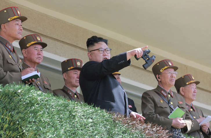 In this undated photo distributed on Friday, April 14, 2017, by the North Korean government, North Korean leader Kim Jong Un, center, watches a military drill at an undisclosed location.