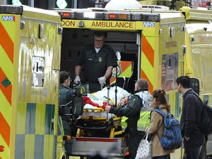Paramedics help a victim into the back of an ambulance at Westminster Bridge