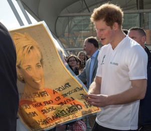 Prince Harry is reads a message written on the back of a picture of his mother, Princess Diana
