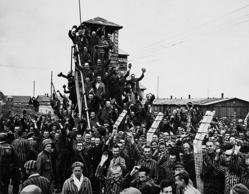 (ITALY MAGAZINES OUT) Prisoners at German Concentration Camp wave to the soldiers of the Seventh U.S. Army coming to liberate them. Dachau, 30th April 1945 (Mondadori Portfolio/Getty Images)