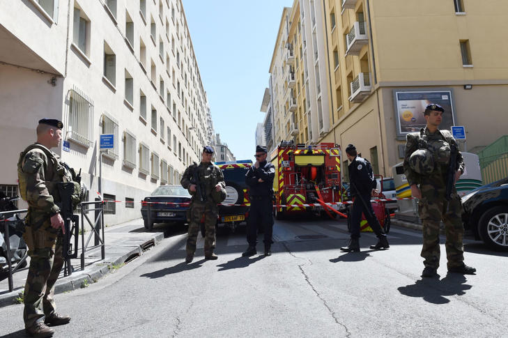 French soldiers, policemen and firefighter vehicles are seen at the site of a police search at the home of one of the two men arrested, as they were suspected of preparing an attack just days ahead of the first round of France's presidential vote on April 18, 2017 in the third district of Marseille.