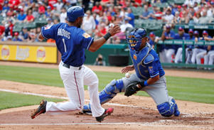 Texas Rangers' Elvis Andrus (1) scores a run as Kansas City Royals catcher Salvador Perez (13) fails to control the ball at home during the second inning of an exhibition baseball game Saturday, April 1, 2017, in Arlington, Texas.
