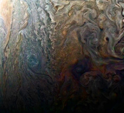 "Slide 3 of 11: This enhanced-color image of a mysterious dark spot on Jupiter seems to reveal a Jovian ""galaxy"" of swirling storms."