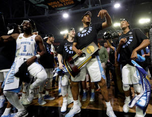 North Carolina's Kennedy Meeks holds the championship trophy as he celebrates with his teammates after the finals of the NCAA college basketball tournament against Gonzaga, on April 3, in Glendale, Ariz. North Carolina won 71-65.