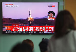 People watch a television news showing file footage of a North Korean missile launch, at a railway station in Seoul on April 5, 2017.