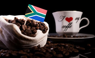 South African flag in a bag with coffee beans isolated on black background