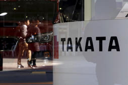 A logo of Takata Corp is seen with its display as people are reflected in a window at a showroom for vehicles in Tokyo, Japan November 6, 2015. Japan's Takata Corp slashed its full-year earnings forecast on Friday as major customer automakers distance themselves from its air bag inflators, which are at the centre of a massive global safety recall.